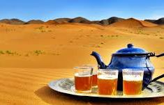 Part of the life of a Bedouin woman - teapot and glasses filled with tea sitting in a desert