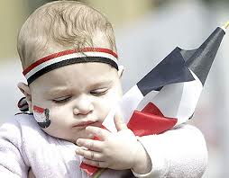 Born in Egypt - Baby with red, white and black headband, with Egyptian flag painted on cheeck carrying a small flag of Egypt