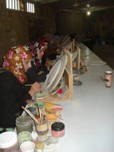 Jordanian women at a table making mosaics in Madaba