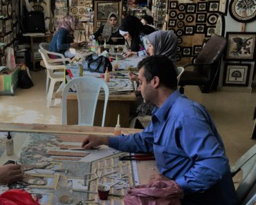 Fouad, a man from Idlib, Syria, working on a mosaic at a workshop in Jordan