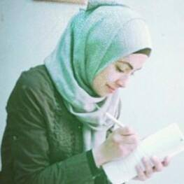 Haneen Owda, a young woman from Nablus, Palestine in a green coat and green hijab, writing in a notebook