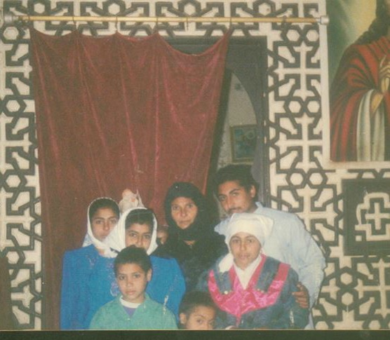 Egyptian mother, three daughters and three sons, mother in all black, children in blue, green and white