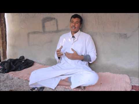 Speaking About The Bedouin Perspective On Life Hemaid Is Dressed In A White Robe Sitting On Light Red Rug In Front Of A Concrete Wall At His Home