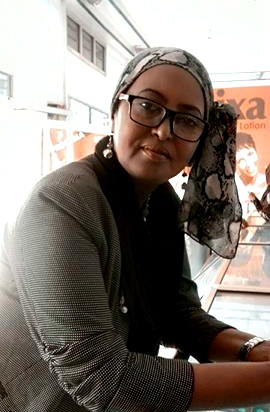 Zahra Saleh, the author of this piece, in a grey sweater with a multicolored headscarf knotted on the side
