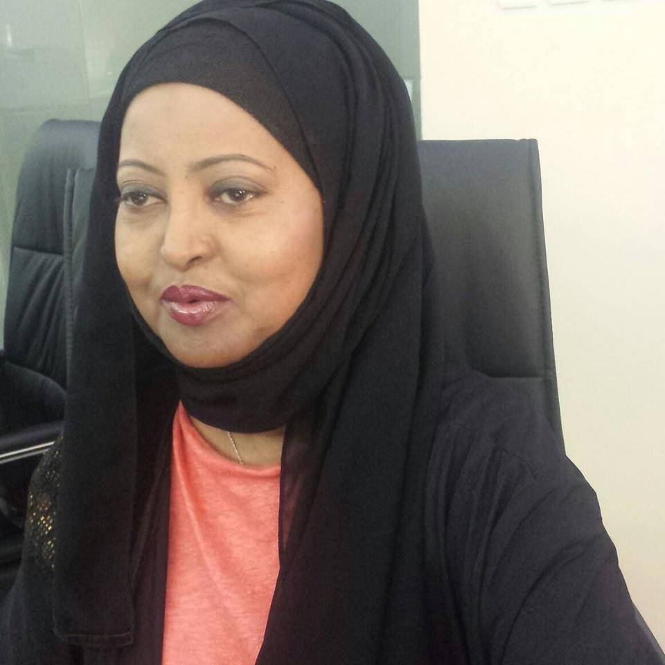 Somalian Muslim Woman Sitting In A Black Desk Chair Wearing An Orange Blouse With A Black Jacket And Black Scarf Over Her Head