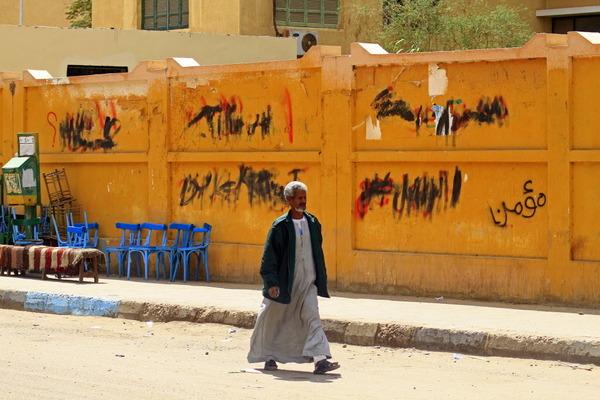 Revenge killings - Man in a jellabeya (long robe) walking down a sandy street in front of an orange metal wall with black writing on it