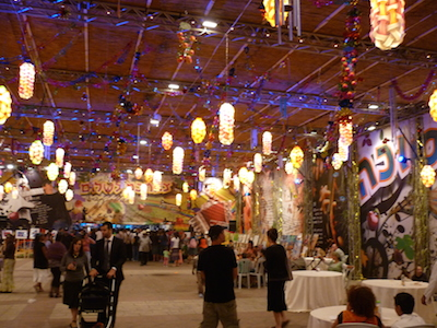 Sukkot in Israel - the inside of a large, elaborate Sukkah, with lanterns hanging from the ceiling, tables on the floor and people milling about