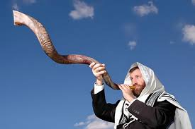 Yom Kippur in Tiberias - Jewish man with a white scar on this heading, outside holding a long, twisting ram's horn
