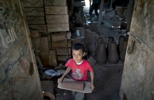 Boy carrying heavy object as one of the working children in Egypt
