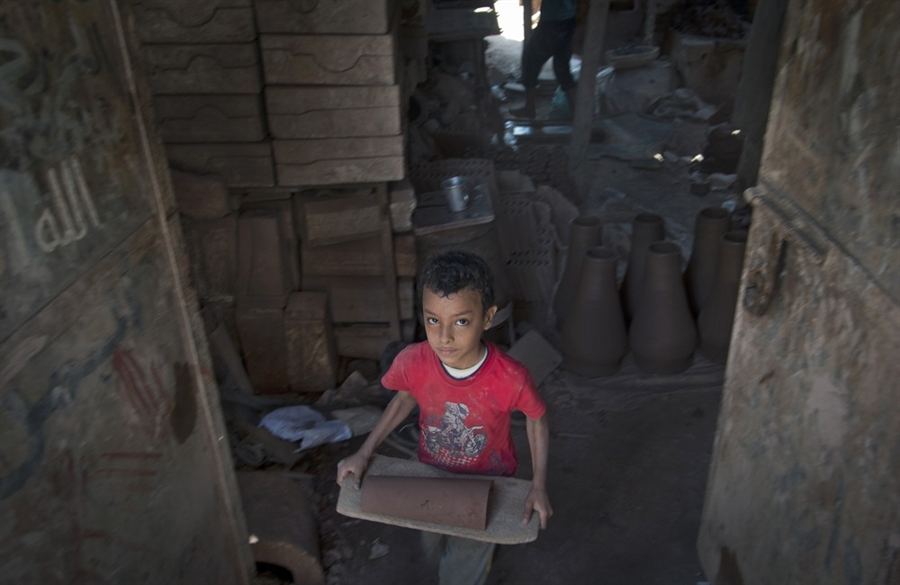 As One Of The Working Children In Egypt, A Small Boy Carries Heavy Objects