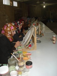 Jordanian women at a table making mosaics in Madaba