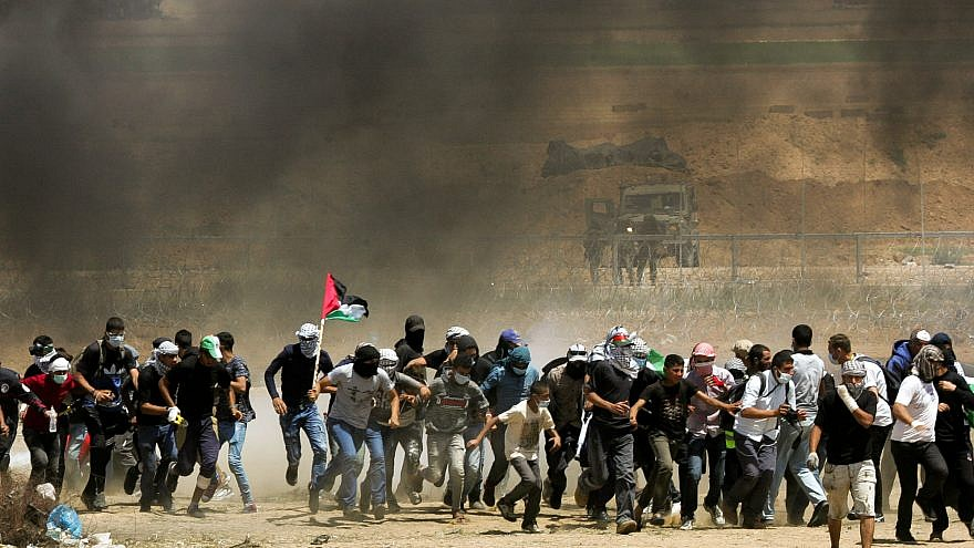 Kibbutz Beit Zera - violence in Gaza, several men running through black smoke waving the Palestinian flag