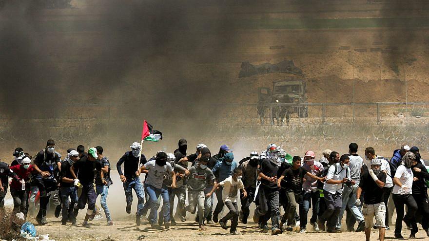 Kibbutz Beit Zera - violence in Gaza, several men running through black smoke waving the Palestinian flag